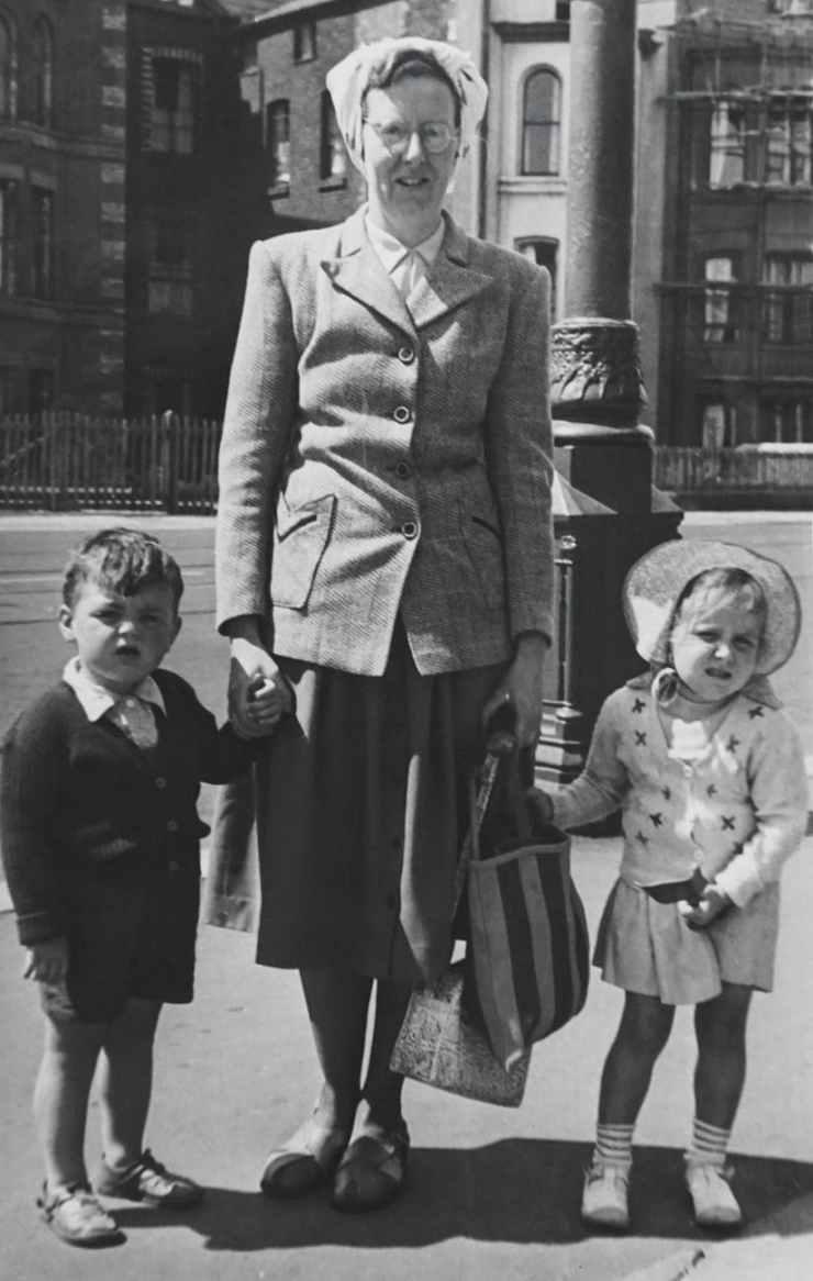 woman holding children s hands
